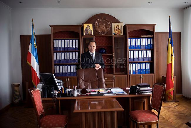 REPUBLIC OF MOLDOVA, Gagauzia, Comrat, 2009/06/27..Mikhail Formuzal Macar, current Bashkan of Gagauzia in his office at the seat of government of the autonomous province. On the left, the flag Gagauz, Moldovan flag on the right, under the protection of the Bulgarian Orthodox Church..© Bruno Cogez..REPUBLIQUE MOLDAVE, Gagaouzie, Comrat, 27/06/2009..Mikhail Macar Formuzal, actuel Bachkan de Gagaouzie dans son bureau au siege du gouvernement de la province autonome. A gauche, le drapeau gagaouze, a droite le drapeau moldave, sous la protection de l'eglise orthodoxe bulgare..© Bruno Cogez