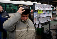 Pedestrians in Moscow get off a bus and walk past street flyers selling apartments, furniture and services. . .Picture by Justin Jin.