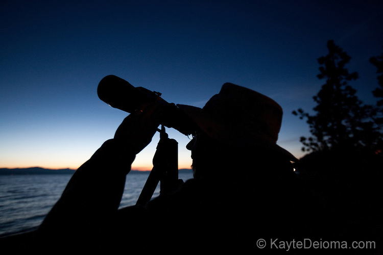 A man looking through a telescope at the night sky from a beach on South Lake Tahoe, California