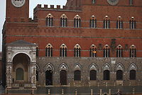"""Siena: In a rainy day, a view of the façade of the ancient """"Palazzo Pubblico"""" (Public Palace) and of a part of the adjacent ancient """"Torre del Mangia"""" (Tower of the Eater) in piazza del Campo (Field square). There are a couple of persons with umbrellas on the right bottom. This image is a slight enlargement of part of the original photo."""