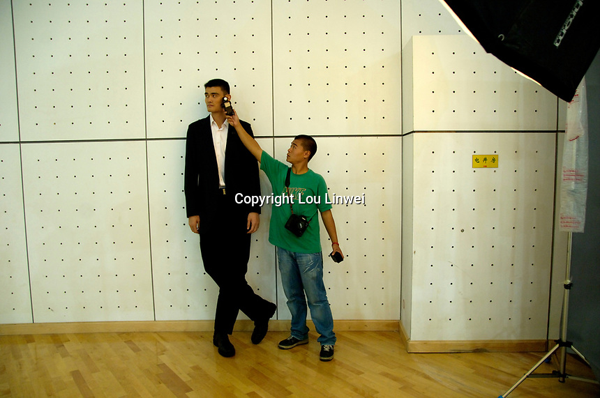 A photography assistant uses a light meter while Yao Ming poses for a photographer from ESQUIRE(China) Magazine in an indoor basketball court in Beijing, China. September 4, 2006  (photo by Lou Linwei/Sinopix)