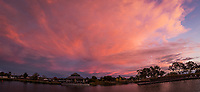 Multiple images combined into a panoramic view of the lagoon at a city park under glowing clouds at sunset.