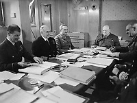 Winston Churchill and his Chiefs of Staff around a conference table aboard SS QUEEN MARY en route to the USA, May 1943. Seated around a conference table aboard the SS QUEEN MARY are, left to right: Air Marshal Sir Charles Portal, Admiral of the Fleet Sir Dudley Pound, General Sir Alan Brooke, Mr Winston Churchill. Prime Minister Churchill is presiding over the meeting at the end of the table. may 1943