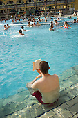 Young man reading a book, Szechenyi thermal baths, Budapest.