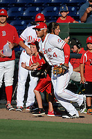 Second baseman Yoan Moncada of the Greenville Drive runs onto the field with a youth player in a game against the Rome Braves on Monday, June 15, 2015, at Fluor Field at the West End in Greenville, South Carolina. The Cuban-born 19-year-old Red Sox signee has been ranked the No. 1 international prospect in baseball by Baseball America. (Tom Priddy/Four Seam Images)