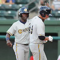 Outfielder DeAngelo Mack (11), left,  of the Charleston RiverDogs congratulates Kyle Higashioka (9) for batting him in with a home run in a game against the Greenville Drive on May 27, 2010, at Fluor Field at the West End in Greenville, S.C. Photo by: Tom Priddy/Four Seam Images