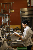 Culinary Arts student Alexandra Gilpin reviews recipe notes during Chef Noah Miller's A la Carte Kitchen and Culinary Skill Development laboratories in Lucy Cuddy Hall's Bakery.