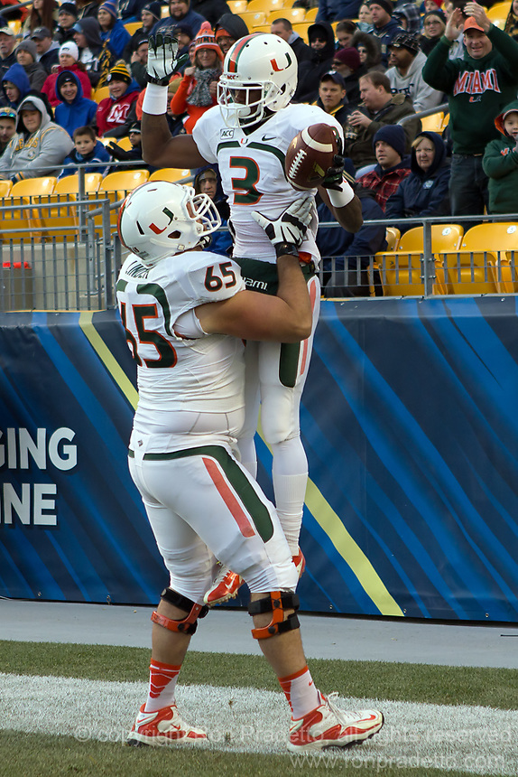 Miami offensive lineman Brandon Linder (65) lifts Miami wide receiver Stacy Coley in the air after Coley's 32-yard touchdwon catch. The Miami Hurricanes defeated the Pitt Panthers 41-31 at Heinz Field, Pittsburgh, Pennsylvania on November 29, 2013.