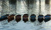 Hampton Court Palace; winter funfare. A row of small wooden boats in the river.