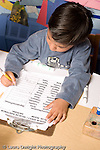 Education Preschool 4-5 year olds start of day boy signing in on sheet of names vertical