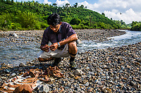 Sitting by a stream, vet Dr. Myo Min Aung looks at the remaining bones of deceased baby elephant Mi Chaw which he excavated in order to keep a memory of her at his home, at Thayatsan elephants camp. A group of bamboo cutters working in the jungle heard a wild elephant screaming near their work site. Afraid of a possible encounter, they made noises to chase it away. It is not unusual for wild elephants to come very close to human territory in Myanmar's forests due to deforestation from decades of industrial logging and plantations. Too late, they realised they had scared away a female elephant who had just given birth, leaving her newborn calf behind. Feeling sorry for the newborn, the villagers called Dr Myo Min Aung, a member of the EERU (Elephant Emergency Response Unit). He named the baby elephant Mi Chaw ('Beautiful Girl') and took care of her as if she were his own daughter.