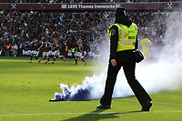 A West Ham safety steward walks onto the pitch to deal with a flare thrown from the crowd during West Ham United vs Brentford, Premier League Football at The London Stadium on 3rd October 2021