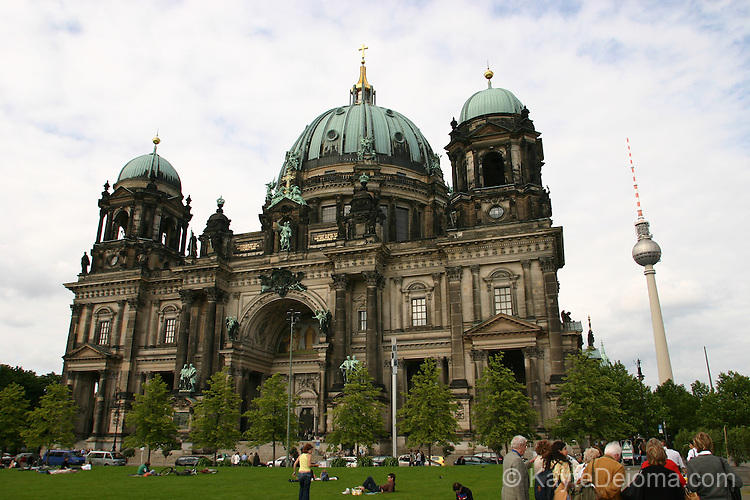 Tourists gather in front of the Berliner Dom, with the Television Tower in the background.  The Protestant cathedral, was built in 1747-1750 and remodelled twice. and was last restored after being damaged in WWII.  Berlin, Germany