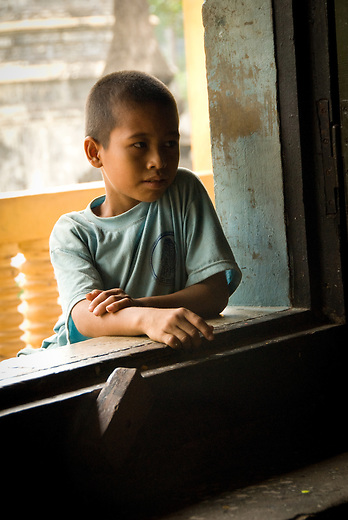 A young Cambodian boy taking a moment to look through a window outside a Buddhist Temple.  Inside, visitors come to show respect and appreciating to Buddhist monks for sharing their sacred places with them.