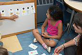 MR / Schenectady, NY. Zoller Elementary School (urban public school). Kindergarten classroom. Student teacher reviews Spanish language flashcards with a small group of native Spanish speakers. MR: She4, Fue3. ID: AM-gKw. © Ellen B. Senisi.