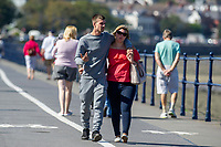Pictured: A young couple during the sunny weather at Mumbles, near Swansea, Wales, UK. Thursday 19 September 2019