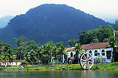 near Angra dos Reis, Brazil. Typical old fazenda ranch house with palm trees and mountains behind.