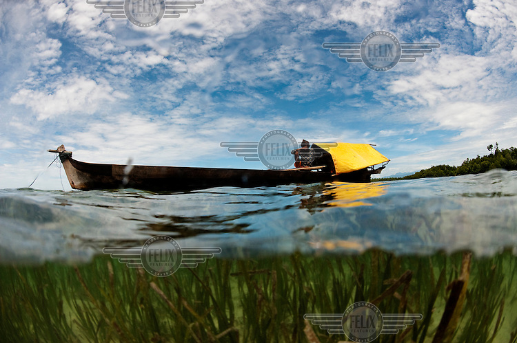 A Bajau fisherman sits in the stern of his boat in the shallows off Sulawesi. The Bajau (Bajo) Laut are an ethnic group of Malay origin, they have for centuries lived out their lives almost entirely at sea, plying a tract of ocean between Malaysia, the Philippines and Indonesia.