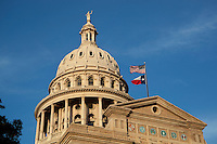 The Texas State Capitol Building in Austin with the US and Texas flags flying in the brisk wind.