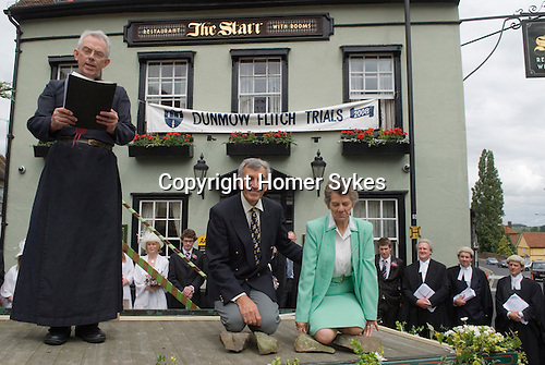 Dunmow Flitch Trial. Great Dunmow, Essex.  UK 2008. .Successful couple kneel on stones to be awarded the Flitch of Bacon by Trial Chaplain Vicar of  Great Dunmow,David Ainge.