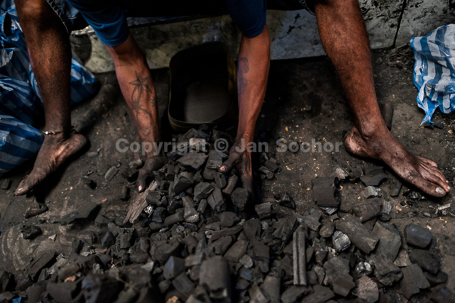 An Afro-Colombian man divides charcoal into small plastic bags to be sold in the market of Bazurto in Cartagena, Colombia, 19 December 2017. Far from the touristy places in the walled city, a colorful, vibrant labyrinth of Cartagena's biggest open-air market sprawls to the Caribbean seashore. Here, in the dark and narrow alleys, full of scrappy stalls selling fruit, vegetables and herbs, meat and raw fish, with smelly garbage on the floor and loud reggaeton music in the air, the African roots of Colombia are manifested.