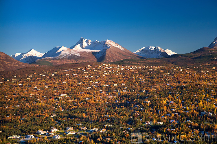 Aerial view of the Anchorage hillside showing housing developments built in front of the Chugach State park boundry, Chugach mountains in the background.