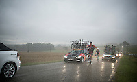 Daniel Oss (ITA/BMC) (trying to) putting on a rain jacket in a full blown thunderstorm<br /> <br /> 2014 Tour de France<br /> stage 19: Maubourguet - Bergerac (208km)