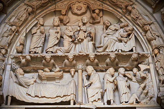 """North Porch, Left Portal (Incarnation Portal), Tympanum- Gifts of the Magi and Dream of the Magi c 1194-1230, from the Cathedral of Chartres, France. At left is the Adoration of the Magi (Matthew 2:1)..Two Magi (crowned) stand at left, holding jars. One has a beard and the other is clean-shaven. The third Magus (bearded) kneels, handing a round object to the Christ Child, who sits on Mary's lap in the middle of the composition. Above them is the star of Bethlehem between two angels holding scrolls..At right is the Dream of the Magi. (Matthew 2:12).Two of the Magi (bearded, still crowned) lie sleeping on a bed at the lower right. The third Magus (beardless) appears behind them, with his eyes closed and his head propped up in his hand. Above is an angel with a scroll, one of the pair of angels who flank the star of Bethlehem at the top of the tympanum..Surrounding the central scene is the Inner archivolt. It contains angels holding candlesticks standing on clouds. Below The Virgin Mary (veiled) lies on a bed that is parallel to the panel plane. She raises one hand. The Christ Child (in swaddling clothes) is in a manger above the bed. Above him are the heads of the ox and the ass. They are probably a reference to Old Testament verses thought to be prophecies of the coming of the Messiah. Isaiah 1:3 says, """"The ox knows his owner and the ass his maker's crib."""" There is a similar verse in Habakkuk. The apocryphal Protevangelium of James mentions only the ass. The Gospel of Pseudo-Matthew also says that an ox and an ass worshiped the Christ Child in the manger..Above are angels leaning out of a cloud and holding a long scroll.. A UNESCO World Heritage Site. ."""