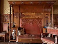 A marquetry settle with built-in shelving, designed by Gaspar Homar, has retained its colour and decoration surprisingly well considering it has had over 100 years of constant use by the Navas family