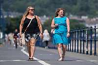 WEATHER PICTURE WALES<br /> Pictured: Two women walk down the seafront in Mumbles, near Swansea, Wales, UK. Thursday 22 July 2021<br /> Re: High temperatures and sunshine has been forecast for most of the UK.