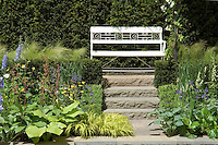 White garden bench at top of stone steps in perennial garden against privacy hedge