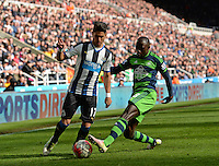 Modou Barrow of Swansea City (right) tackles Ayoze Perez of Newcastle United during the Barclays Premier League match between Newcastle United and Swansea City played at St. James' Park, Newcastle upon Tyne, on the 16th April 2016
