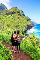 Hikers embrace as they look at the Napali (or Na Pali) coastline from the Kalalau Trail near Hanakapi'ai Beach, North Kaua'i.