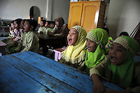 Children sing at a makeshift school in Porong, where some of the victims of the mud flow attend classes. Since May 2006, more than 10,000 people in the Porong subdistrict of Sidoarjo have been displaced by hot mud flowing from a natural gas well that was being drilled by the oil company Lapindo Brantas. The torrent of mud - up to 125,000 cubic metres per day - continued to flow three years later.