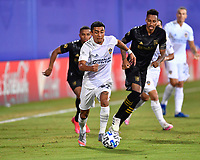 LAKE BUENA VISTA, FL - JULY 18: Julian Araujo #22 of LA Galaxy dribbles away from Mark-Anthony Kaye #14 of LAFC during a game between Los Angeles Galaxy and Los Angeles FC at ESPN Wide World of Sports on July 18, 2020 in Lake Buena Vista, Florida.