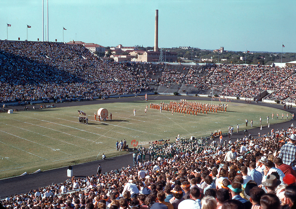 In this vintage photo from October, 1955, the US Military Color Guard with the UT Big Bertha Drum leads the University of Texas Longhorn Band during half time show.
