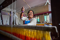 Nepal, Kathmandu. Sabah, a non profit, women workers in clothing factory. Woman weaving on loom. Her husband left her for another women and she was able to raise her two sons by working here.