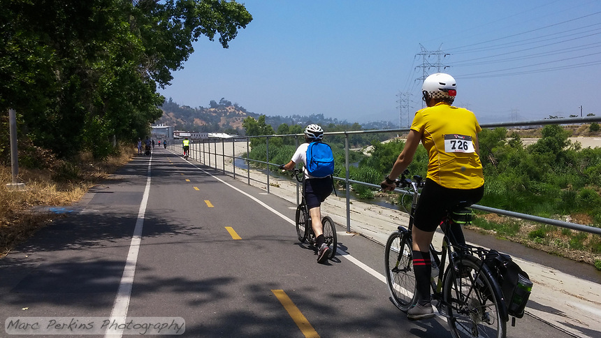Heading north on the Los Angeles River Greenway Trail during the 2017 (17th annual) Los Angeles River Ride.  Many bicyclists can be seen ahead of Holland on his kick scooter and Michelle on her Terry Burlington city bike, and the river's beautiful greenery and water can be seen in the background.