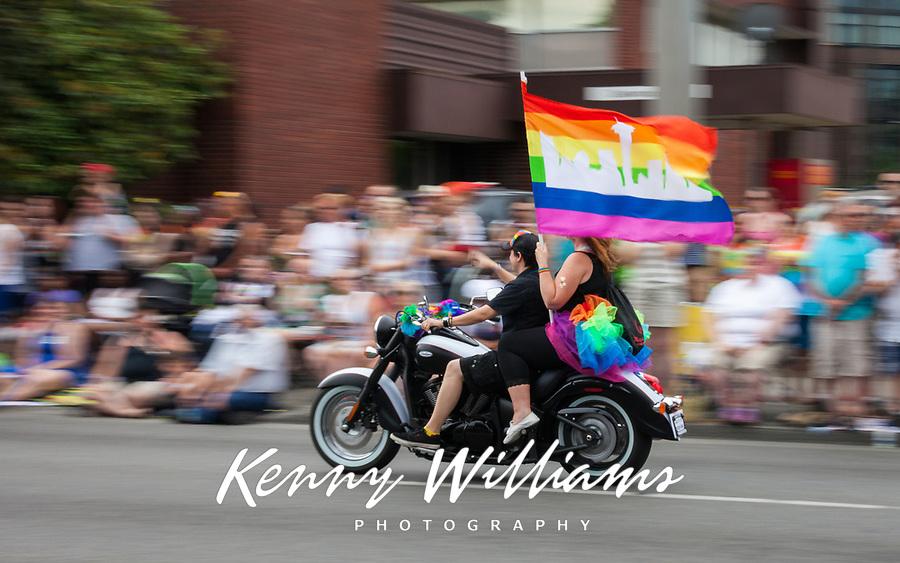 Two Women Riding Motorcycle Holding Rainbow Pride Flag, PrideFest, Seattle, WA, USA.