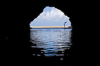 A woman holds a pareo in the wind at the mouth of a sea cave, Kalalau Beach, Na Pali Coast, Kaua'i.