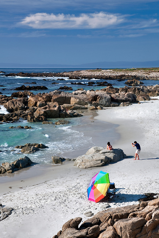 Beach umbrella and beach with man taking picture of family. 17 Mile Drive, Pebble Beach, California