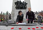 Olympian Anastasiya Muntyanu and Parapan American Games athlete Chantal Beauchesne place wealths at the foot of the National War Memorial during the Remembrance Day ceremony in Ottawa, November 11, 2015.<br /> COC Photo by Jason Ransom