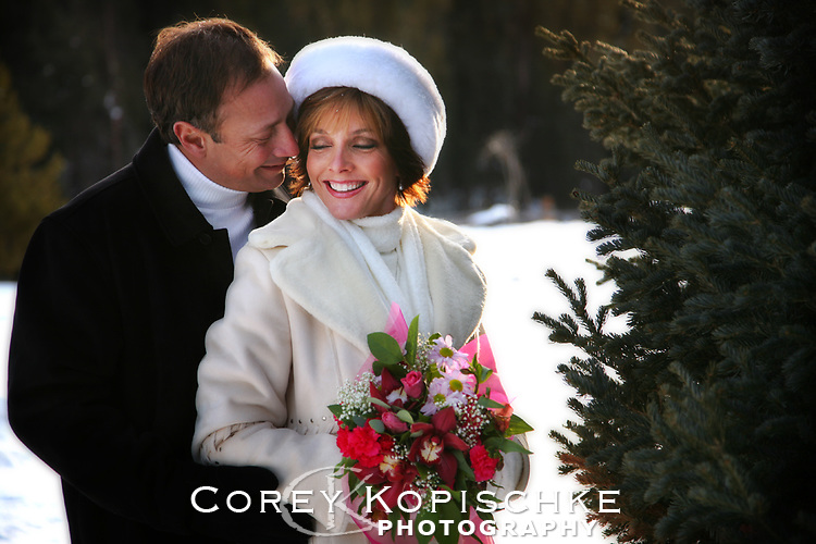Bride and groom snuggle during outdoor formals in the snow at Elk river guest ranch in northern Colorado.