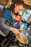 A woman stirs a saucepan of soup on the kitchen stove while breastfeeding her 20 month old toddler who is in a sling.<br /> <br /> 07/02/2013<br /> Hampshire, England, UK