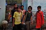 A group of young musician going out for performance from Katputly colony in New Delhi, India. 14.11.2009. Kathputly colony is a slum area in West Delhi. This slum seems like any other slum areas of modern India with dysfunctional electricity, non existing sanitation and poverty. As a part of Delhi, this is also ailed with water crisis. Large families live their lives crammed together in a single room with all the odds which complement poverty. One thing which differentiates this slum with any other is the people living in the colony. Nearly everybody in this slum is a traditional performing artist; and they have been migrating to this area for last 50 years from different parts of the country for a better livelihood. They are magicians, acrobats, jugglers, puppeteers, dancers and musicians. These artistes perform in star rated hotels, marriage ceremonies of the richer section, functions, and festivities all around the country and the world. Most of the artisans I met here, have performed in Europe and America but such opportunities are rare to come by. They struggle to keep their art form alive. They say that they don't get any help or support from the government for their basic needs and for the well being of the Kathputly colony -  though they have uphold the prestige of the country internationally. Polluted air, dirty alleys smelling of urine, colourful dress and sound of music characterise Kathputly colony, which is the one of its kind in India. Arindam Mukherjee