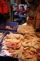 Rows of chicken parts and pork cuts for sale at the Shenzhen Buji agriculture market.<br />