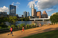 A perfect summer day finds runners and bikers exercising on Austin's most popular hike and bike trail, the Ann and Roy Butler Hike and Bike Trail while rowing teams race up and down Lady Bird Lake. Ten miles of trails border Lady Bird Lake in downtown Austin and serve as a social hub for runners, walkers and cyclists.