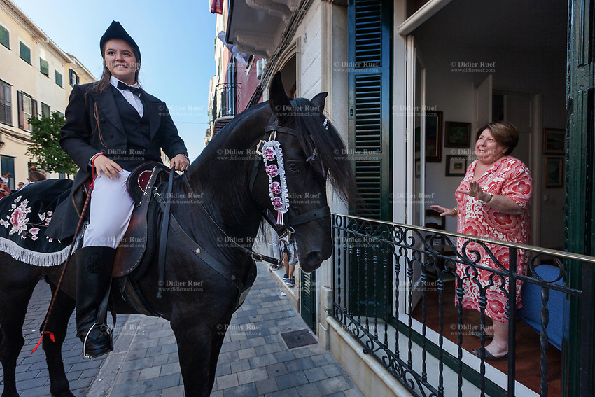 "Spain. Balearic Islands. Minorca (Menorca). Mahon. A horsewoman chats with an elderly woman during the  ""Festes de la Mare de Déu de Gràcia"" , a traditional summer festival. The Menorquín is a breed of horse indigenous to the island and is closely associated with the doma menorquina style of riding. The riders wear black and white and most of their horses (adorned with ribbons and multi-coloured rosettes) are of the highly-considered Menorcan breed. The riders and their horses parade through the streets, and these magnificent and remarkably calm horses rear up on their hind-legs to the delight of the crowd. Horses and riders are at the centre of local fiesta celebrations, in a tradition that may go back to the 14th century and incorporate elements of Christian, pagan and Moorish ritual. Some 150 riders participate in the festival in Mahón. Maó (in Catalan) and Mahón (in Spanish), written in English as Mahon, is a municipality, the capital city of the island of Menorca, and seat of the Island Council of Menorca. The city is located on the eastern coast of the island, which is part of the autonomous community of the Balearic. In Spain, an autonomous community is a first-level political and administrative division, created in accordance with the Spanish constitution of 1978, with the aim of guaranteeing limited autonomy of the nationalities and regions that make up Spain. 7.09.2019 © 2019 Didier Ruef"