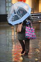 Wednesday 12 February 2014<br /> Pictured: A woman struggles in the wind on Swansea's Oxford Street<br /> Re: People struggle with the high winds in the center of Swansea. The met office has today issued more warnings of extreme weather over the next few days.