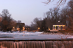 A gazebo along the park on a mill pond and waterfall over a dam in Midwest America, Menomonee Falls Wisconsin